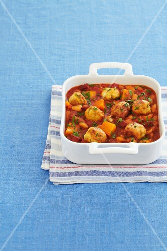 A bake with small dumplings, tomatoes, sweet potatoes and parsley