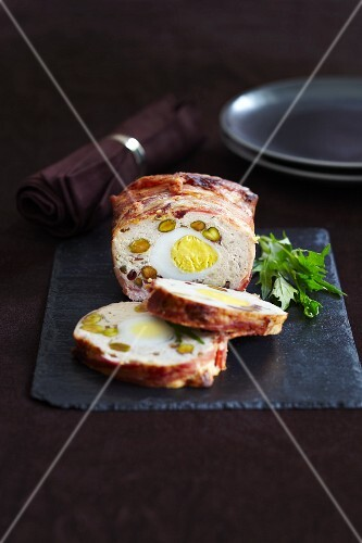 Pork roulade filled with pistachios and eggs wrapped in crispy bacon