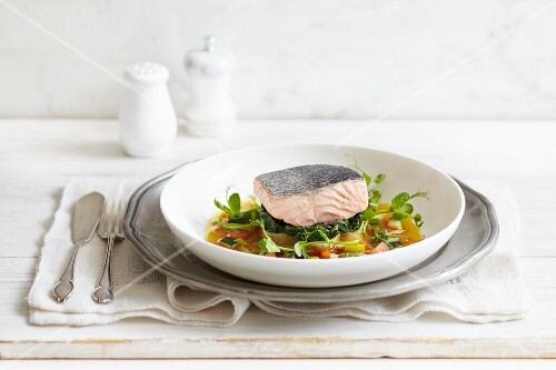 Poached salmon fillet on a bed of vegetables