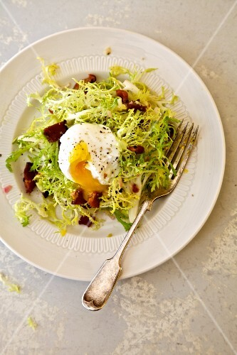 Salade Lyonnaise with frisee lettuce, poached egg and crispy bacon (Lyon, France)