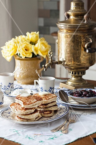 Blinis (honey-yeast pancakes, Russia) with cherry compote and a samowar