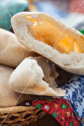 Pita bread in a bread basket, broken