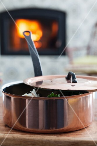 A copper pan in front of a fireplace