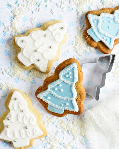Christmas tree-shaped gingerbread and shortbread biscuits with blue and white icing