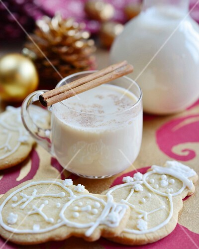 Traditional eggnog with cinnamon sticks and snowmen biscuits (Christmas)