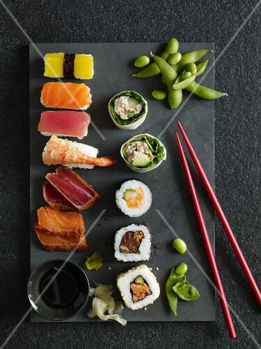Nigiri sushi, California rolls, maki sushi and sashimi on a stone platter