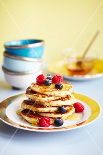 Pancakes topped with blueberries, raspberries and maple syrup (USA)