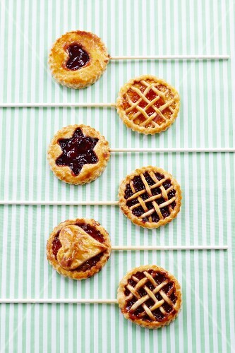 Six jam tarts on sticks decorated with stars, hearts and lattice toppings