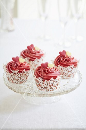 Cupcakes with pink icing and sugar hearts in white butterfly cake cases