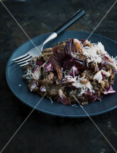 Radicchio risotto with onion confit on a dark plate with a fork