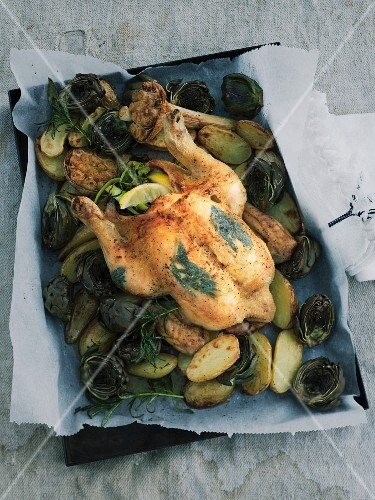 Rosemary chicken with potatoes and artichokes on a baking tray