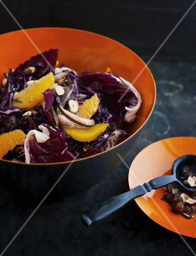 Red cabbage salad with oranges and dates on a dark surface