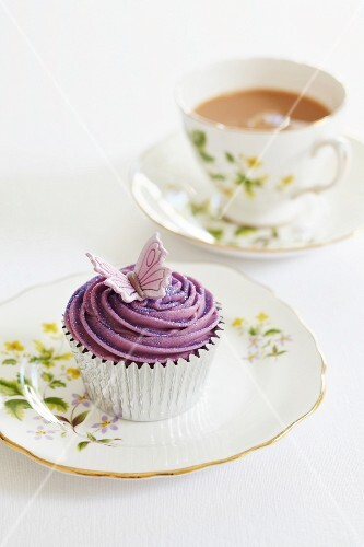 A butterfly cupcake with a cup of tea