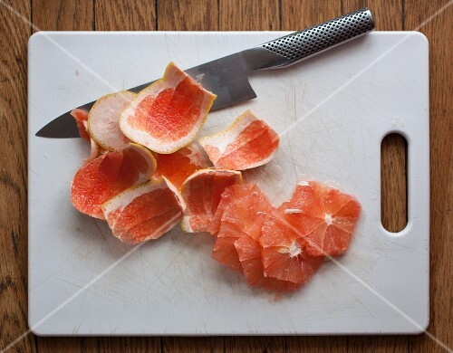 Slices of grapefruit, peel and a knife on a chopping board