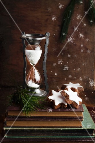 An arrangement featuring an antique sand timer and chocolate and nut Christmas biscuits