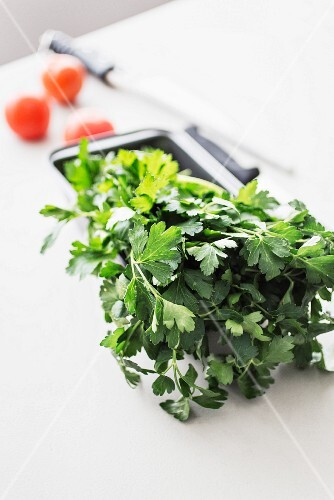 Fresh parsley on a white kitchen table with three tomatoes and a knife
