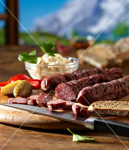 Supper with Kaminwurzen (South Tyrolean smoked sausages), horseradish and Vinschgau bread against a mountain backdrop