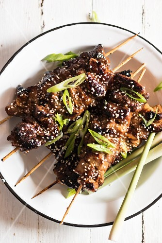 Pork belly skewers with sesame seeds and spring onions