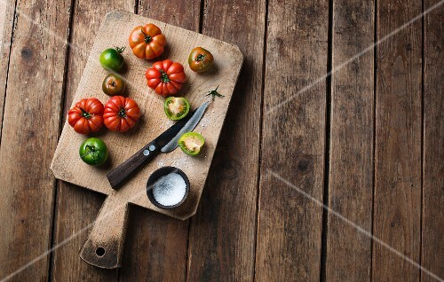 Various tomatoes on a chopping board with salt and a knife