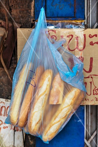 Baguettes in a plastic bag in front of a shop at a market (Vientiane, Laos)