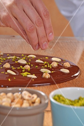 A chocolate bar with nuts and pistachios being made
