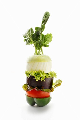 A stack of vegetables made of peppers, tomatoes, aubergines, lettuce, onion and kohlrabi