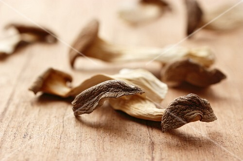 Dried king trumpet mushrooms on a wooden surface