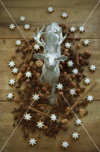 A stag figurine surrounded by nuts, cinnamon stars, cinnamon sticks and star anise