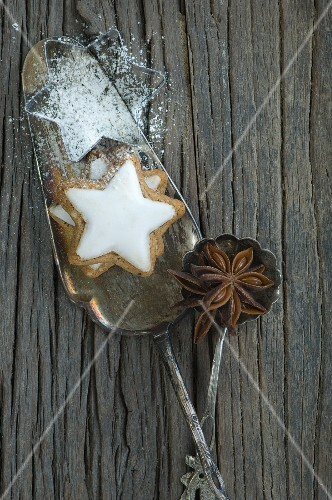 A cinnamon star and a cutter on a cake slices with a star anise on a spoon
