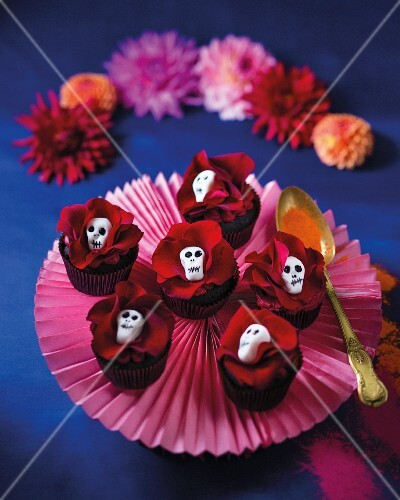 Chocolate cupcakes decorated with red roses and skulls (Mexico)