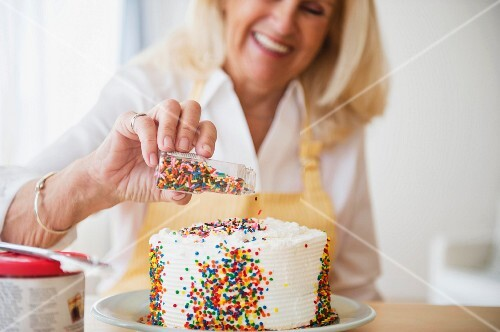 A woman decorating a cake with sugar sprinkles