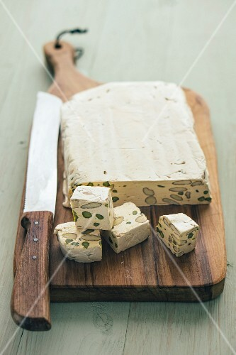 Homemade nougat with pistachios and almonds on a wooden board