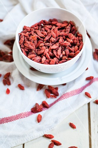 Goji berries in a porcelain bowl on a tea towel