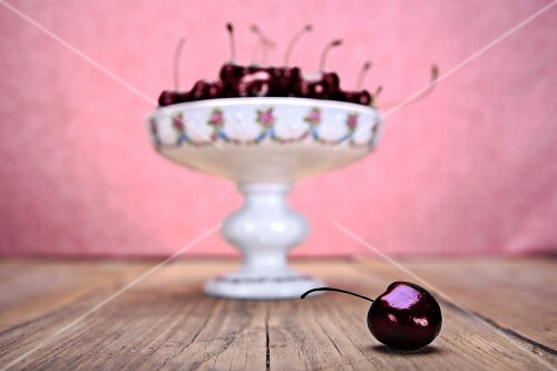 Cherries in a bowl on a wooden table with one cherry in the foreground