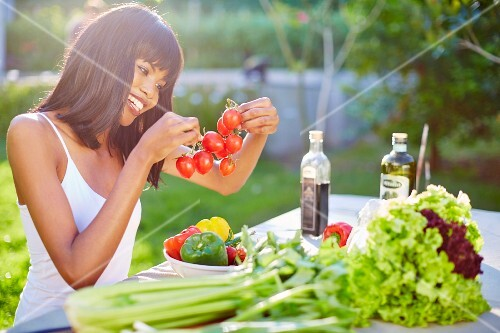 A young woman preparing a vegetables on a garden table