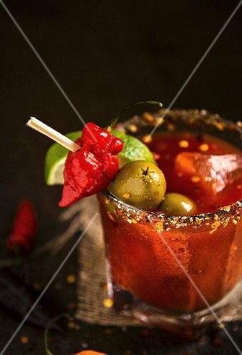 A Bloody Mary with chilli peppers, limes and green olives