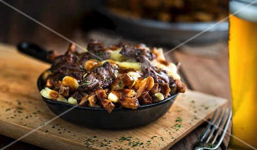 A rustic dishes featuring chips, cheese, pork and gravy