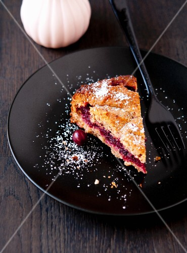A slice of Linzertorte (nut and jam layer cake) with cherries