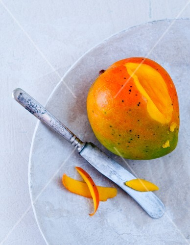 A mango, sliced, on a marble plate