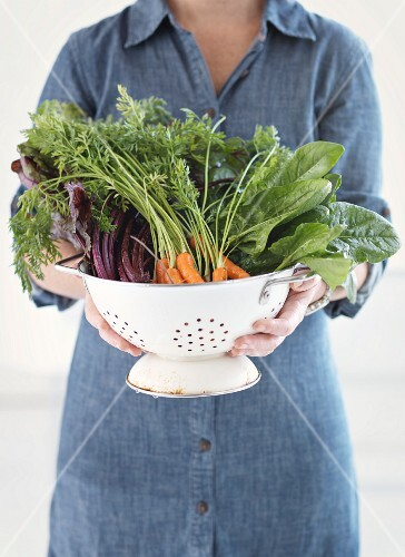 A woman holding a colander of fresh vegetables
