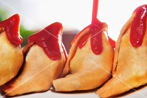 Ketchup being poured over samosas