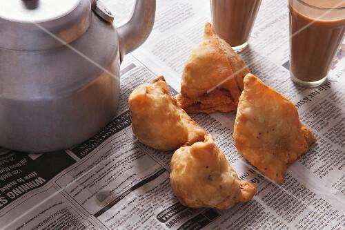 Fresh samosas and tea on newspaper