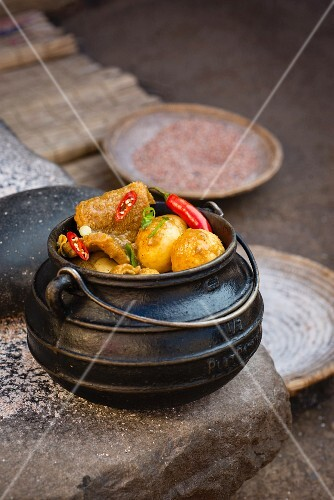 Tripe in chilli sauce with yeast dumplings served in a cauldron