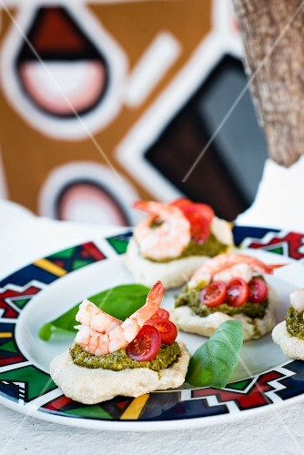 Prawns with basil pesto and tomatoes on mini baked corn bread rolls