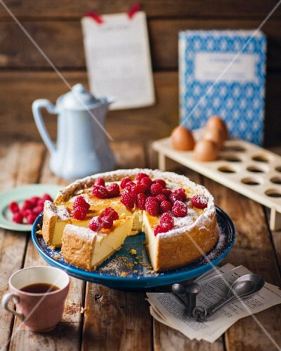 A sliced cheesecake with raspberries served with coffee