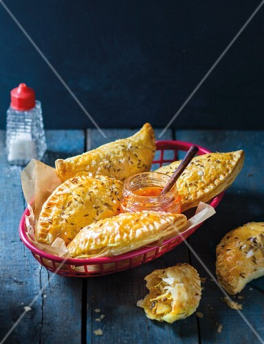 Baked puff pastry parcels with a snoek-potato filling in a bread basket served with sweet chilli sauce