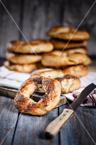 Homemade poppy seed bagels with a knife on a wooden surface