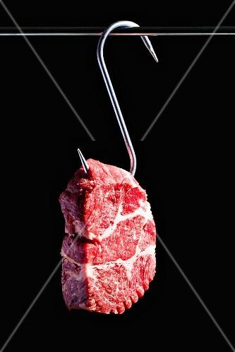 A raw beef steak on a meat hook