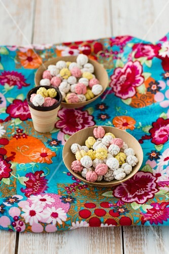 Two bowls of sugared chickpeas on a piece of floral-patterned fabric