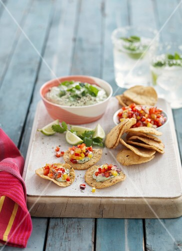 An avocado dip with corn crackers and vegetable salsa